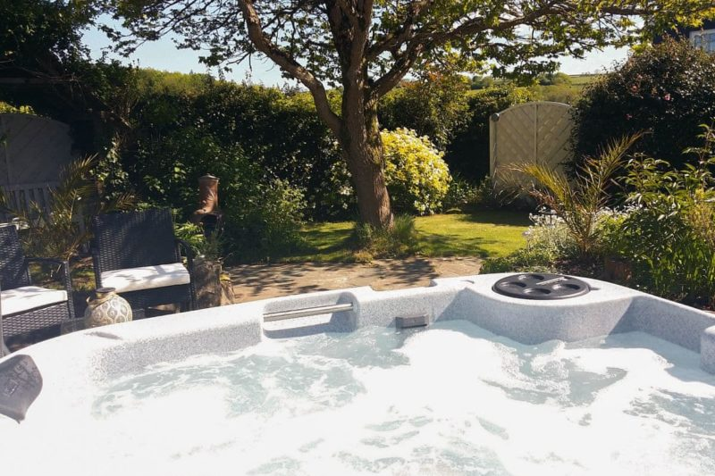 Enjoy the hot tub whilst admiring the well kempt garden | Candlelight Cottage, Littlehempston, near Totnes