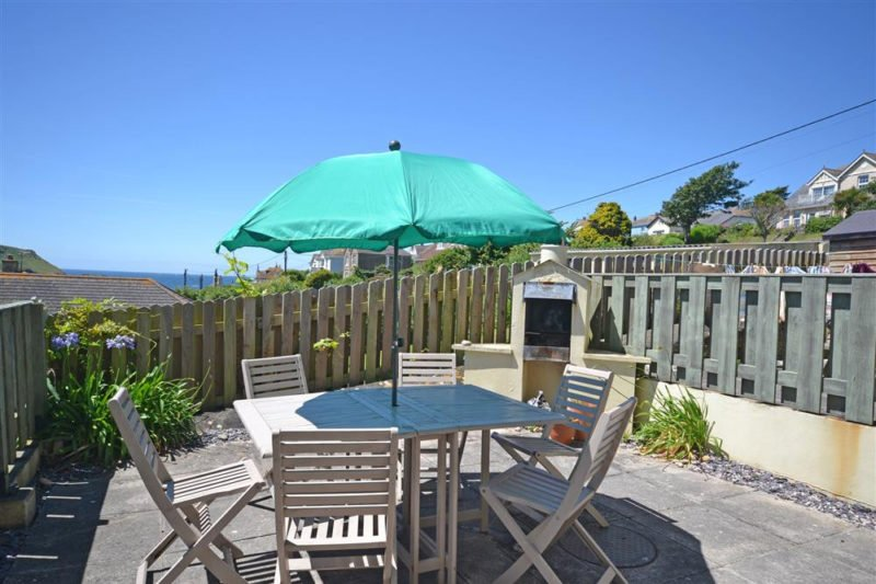 The sunny patio with a barbecue area, to house disposable barbecues, and views of the sea.