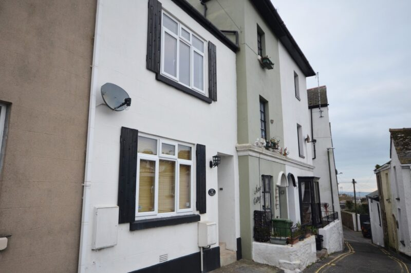 Towards the property, which has traditional black shutters, and is a short stroll to the harbour