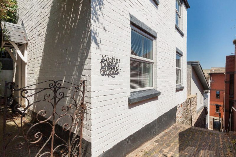 Whitewashed exterior with decking in the garden | Evelyn Cottage, Dartmouth